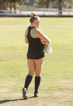 Полненькая футболистка делает растяжку перед тренировкой